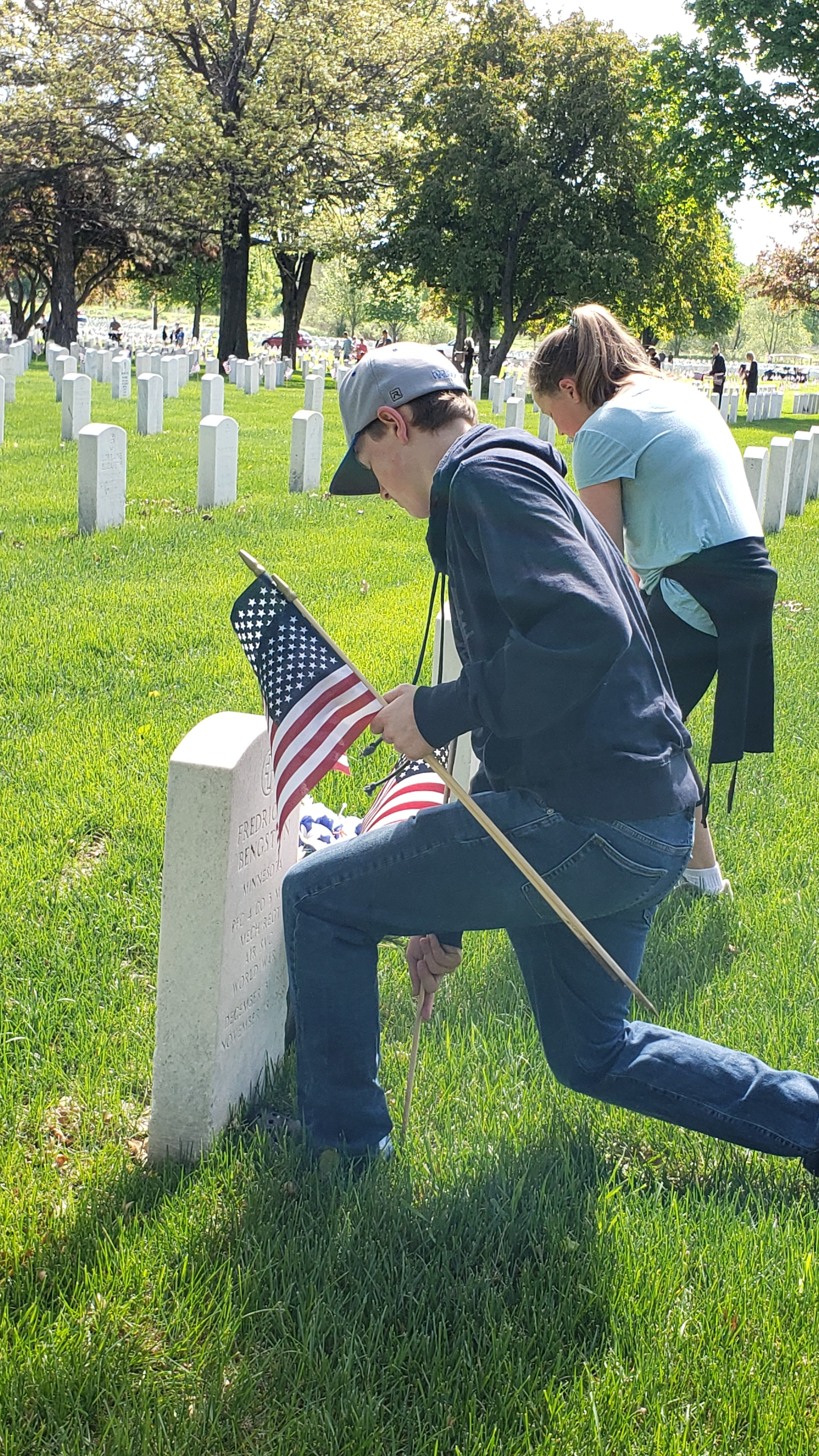 Kids placing flags on headstones at Fort Snelling National Cemetary in Minnesota